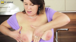 Charming mature with huge melons is masturbating in the kitchen