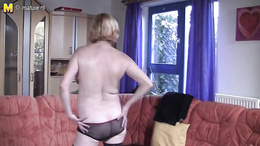 Charming granny is stripping and starts masturbating with a vibrator