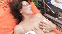 Granny gets horny while sunbathing outside and finger fucks herself