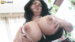 Mature slut with garter licks her huge boobs and fucks with toys