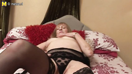 Chubby grandma in blach stockings fucks herself with a toy on the bed