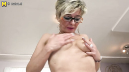 Horny grandma with glasses fingers herself on the kitchen counter