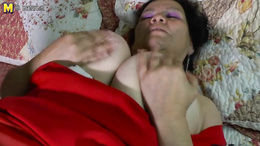 Fat granny squeezes a toy between her huge boobs and sucks it