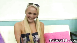 Hot blonde teen with pigtails uses a big dildo to play wih on the sofa